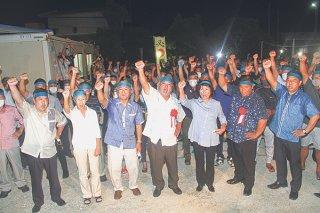 勝利に向けて「頑張ろう」を三唱する前西原陣営の支持者ら=30日夜、祖納の後援会事務所