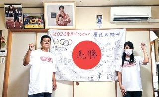 関係者らが寄せ書きした日の丸を飾り、息子を応援した父保さんと母直美さん(左から)=2日、宜野湾市(提供)