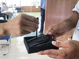期日前投票所の入り口で有権者に配布されている記入用の鉛筆。使い終わると消毒される=4日午前、町構造改善センター