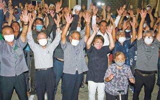 糸数氏(中央)と大勢の支持者が当選を祝い万歳三唱した=8日夜、崎原商店倉庫前