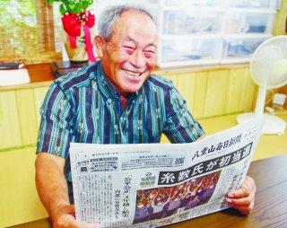 初当選を報じる八重山毎日新聞を手に笑顔をみせる糸数氏=9日午後、祖納の自宅