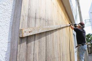 木製の防風戸を補強する市民=11日午前、石垣市大川