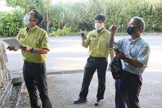 ICレコーダーを手にイシガキニイニイの生息調査をする島村賢正氏(右)と環境省の職員ら=7月9日、ヤエヤマヤシ群落