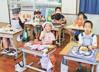 笑顔で弁当を見せる小学部3年の子どもたち=27日午後、八重山特別支援学校