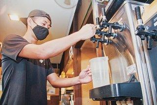 緊急事態宣言後の酒類提供再開に向け、ビールサーバーを洗浄する店舗従業員=27日午前、石垣屋
