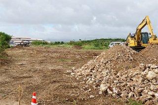 重機を使った伐開工事が始まった旧空港跡地線。奥には石垣市役所新庁舎が見える=6日午後