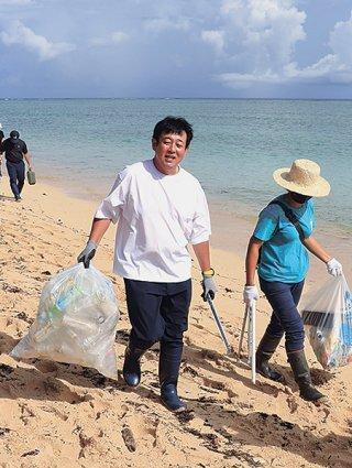 ペットボトルが入ったごみ袋を運ぶ前田亘輝さん=7日午前、西表島中野海岸