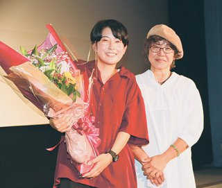 舞台挨拶終了後、花束を手に笑顔を見せる東盛あいか監督と母・朝子さん(左から)=9日午後、桜坂劇場