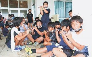 作った横笛を練習する大浜小の児童ら=12日午後、同校