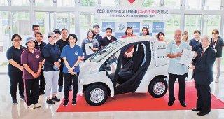 公益財団法人みずほ教育福祉財団から贈呈された配食用小型電気自動車「みずほ号」と石垣市社会福祉協議会の職員ら=13日午後、市健康福祉センター内