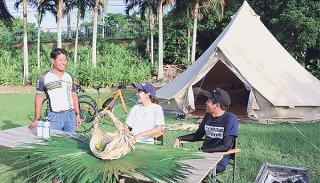 川満陽一代表(左)から、キャンプ道具を用意しなくても気軽に楽しめるキャンプ体験「グランピング」の説明を受けるツアー参加者ら=14日夕、石垣市米原