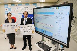 画面に写るAIチャットボット「BEBОT」。PRをする綱川代表と西大舛町長(左から)=21日午後、町役場仮庁舎