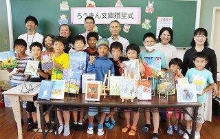 ろうきん八重山地区推進委員会から贈呈された本を手にする吉原小の児童ら=26日午後、同校